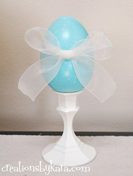 Easter! Dollar Store craft idea. Spray paint a candle stick, paint a plastic egg, tie on sheer ribbon. This would be cute with several eggs together in a window.