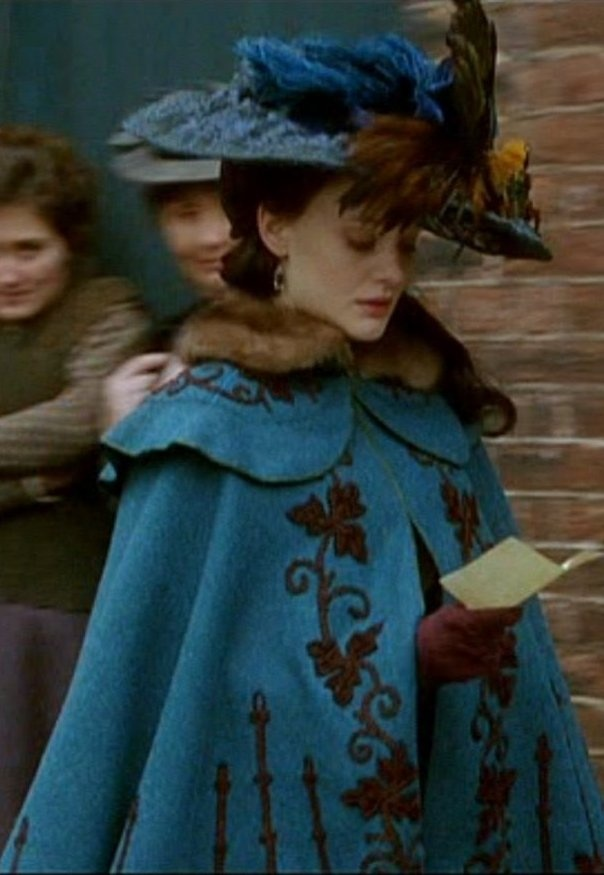 Angel. Late Victorian fashion in some sort of tv series? Beautiful turquoise cape and hat with brown decorations and matching brown gloves.