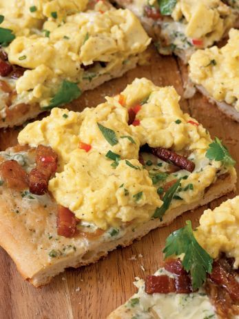 Tarte Flambe with Softly Scrambled Eggs and Goat Cheese : Alsatian tarte flambe is a thin-crust pizza layered with caramelized onion and smoky bacon. Here, Bobby ups the ante with herbs, scrambled eggs and creamy goat cheese.
