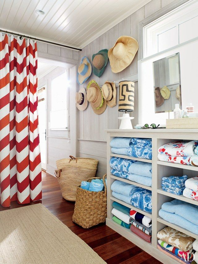 In this Southampton, New York, beach house by interior designer David Netto, a curtain made of a Schumacher chevron stripe provides privacy in the pool cabana's changing room; the table lamp is by Waldo's Designs, and the carpet was custom made by Beauvais.