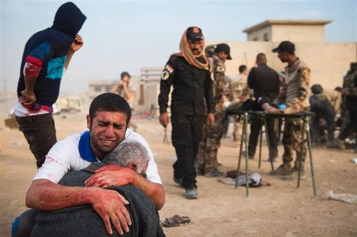 The father and grandfather of 15-year-old Shafiq mourn as Iraqi forces surround his body at an outdoor field clinic in the Samah neighborhood in Mosul on Nov. 13.  A double-barreled mortar attack killed Shafiq and seriously injured his 12-year-old neighbor Mohammed as Iraqi Special Forces continued to battle ISIS forces. ODD ANDERSEN / AFP - Getty Images