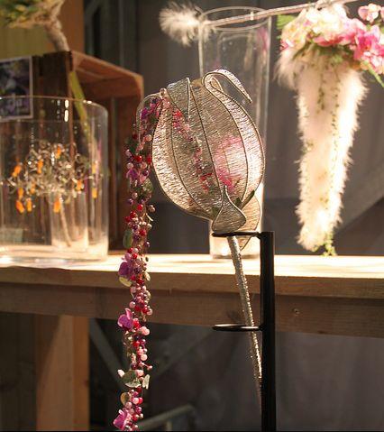 Bruidsboeket gemaakt van zilver wikkeldraad. Vanuit binnen naar buiten hangt een slinger gemaakt van zoetwater parels met paars, roze en rode plastic parelels, Ceropegia Woodii en roze mini orchidee. Binnen in de bloem zit een grote roze orchidee.