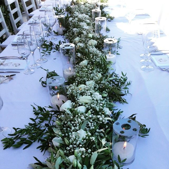 A very exclusive flower decoration of dinner table with fairy lights and olives leaves
