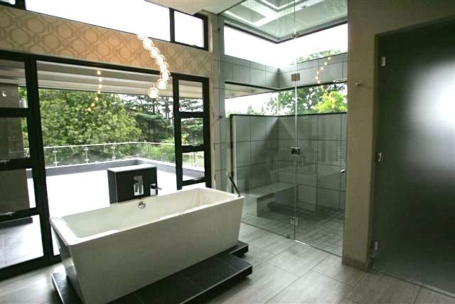Beautiful modern bathroom with stunning view and statement lighting.