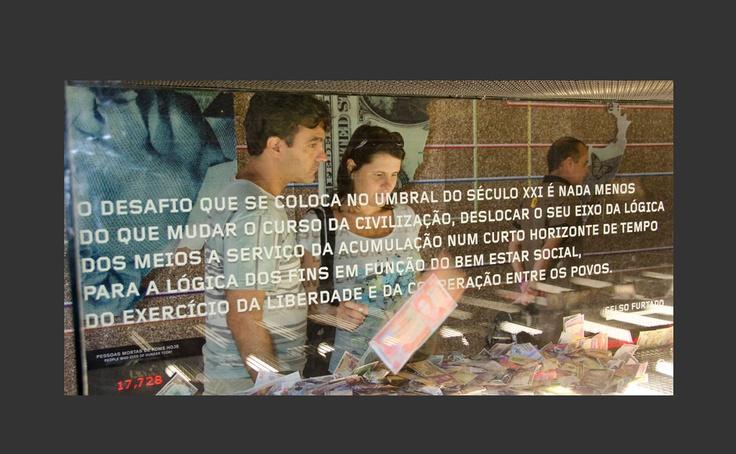 """Um casal de visitantes observa uma longa vitrine na sala nº 2 """"Mundo Dividido"""", onde notas de dinheiro de todas as partes do mundo são espalhadas por um ventilador e ficam aglutinadas nos cantos. (Humanidade 2012, Forte de Copacabana)"""