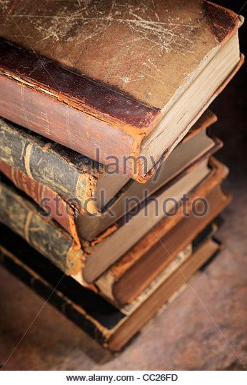 A Stack of old worn and tattered books. Short depth-of-field. - Stock Image
