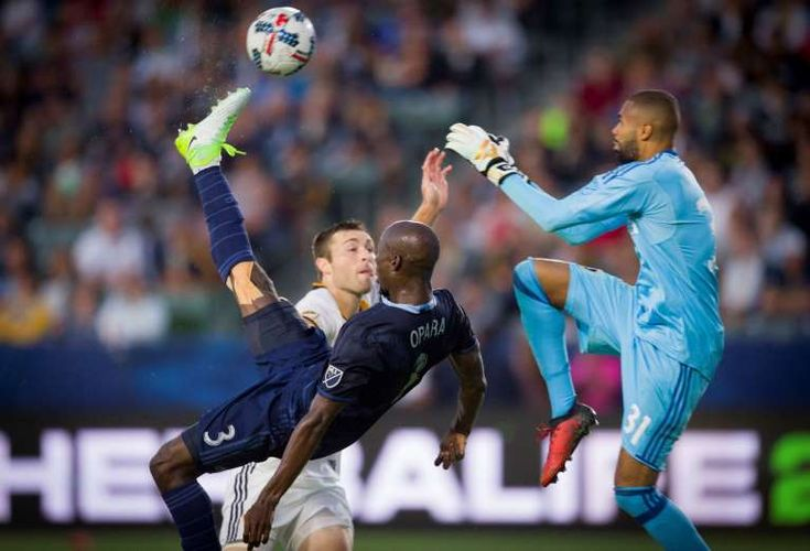 2017 MLS season - December 10, 2018:  AND THE BICYCLE KICK -  Sporting Kansas City's Ike Opara, left, scores a goal off a bicycle kick as LA Galaxy's Clement Diop, right, defends on June 24 in Carson. Kansas City won 2-1.