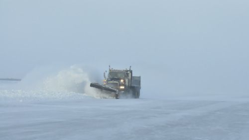 Plowing the snow off of the ice road.