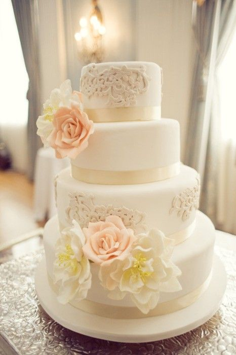 "I like the mix of ""lace"" piping with some fondant flowers. If these flowers were done in various shades of purple (anything from lavender to plum) they would be perfect."