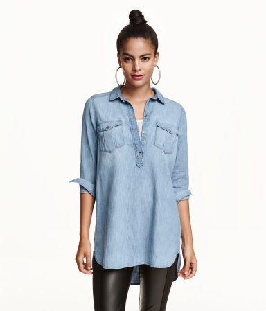 Een lange overhemdblouse van gewassen denim met een turndown boord en een knoopsluiting bovenaan. De blouse is afgerond aan de onderkant en heeft lange mouwen, borstzakken met klep en knoop en een iets langer achterpand.