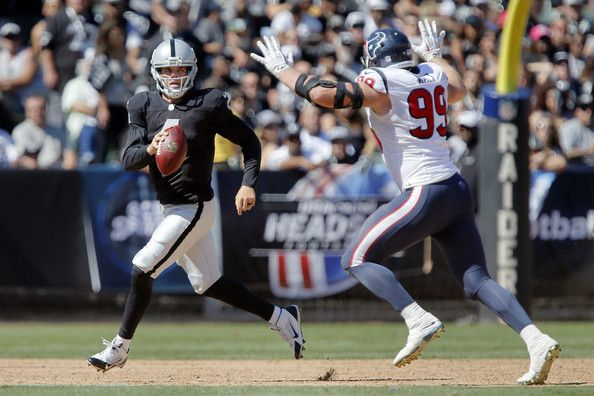 Rookie quarterback Derek Carr #4 of the Oakland Raiders looks for a receiver under pressure from defensive end J.J. Watt #99 of the Houston Texans late in the second quarter on September 14, 2014 at O.co Coliseum in Oakland, California.