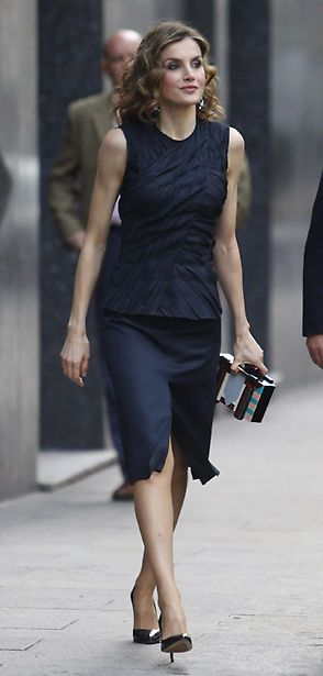 "Queen Letizia premiered a new petrol blue ensemble from Nina Ricci's pre-fall 2016 collection teaming a sleeveless crinkled top (US$1,790) with a matching slit-front a-line skirt. She also debuted an art-deco inspired box clutch by Adolfo Dominguez, earrings from Mango Blue Faceted Crystal Earring (US$24.99),  and Magrit 'Mila' pumps in midnight blue patent leather. ""Famelab España 2016 Scientific Monologues,"" Callao Cinema, May 12, 2016, Madrid, Spain."