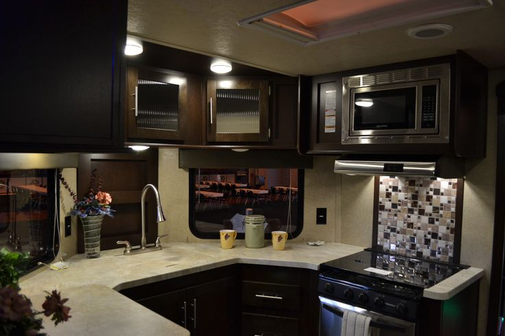 2017 V-Nosed 234VFK front kitchen by Cherokee is a beautiful camper! There are large windows on both sides of the V-shaped nose to allow natural light into the kitchen/living space. The kitchen has a large double door refrigerator/freezer, a sink with a cover, a 3 burner stovetop with an oven and lighted hood, a stainless steel microwave and a ton of gorgeous glass faced cabinets and counter space