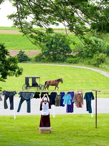 Amish customs..  A woman hangs laundry at Yoder's Amish Home. Tours here explain how Amish use straight pins to fasten their clothing to avoid ostentatious buttons and buckles.