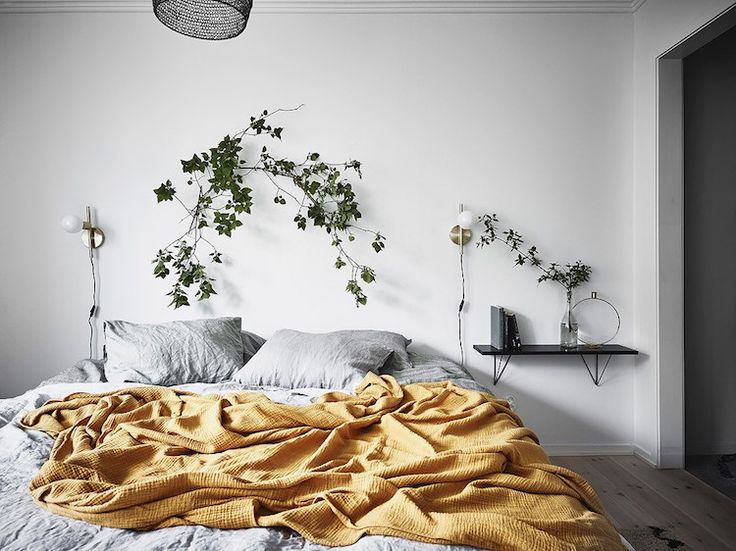 A bedroom with light grey linen and mustard throw