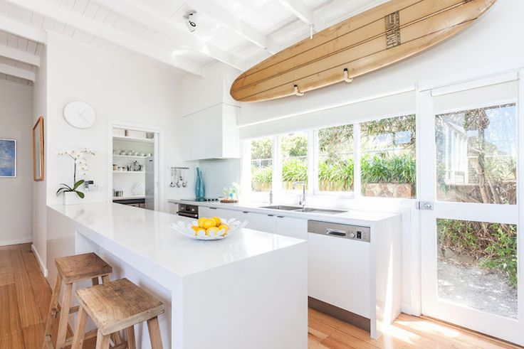 Coastal style kitchen features a surfboard on wall over a bank of windows and white lacquered cabinets fitted with dual sink.