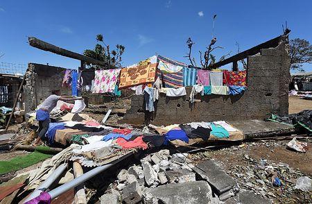 17日、超大型サイクロン「パム」が直撃したバヌアツの首都ポートビラで、倒壊した自宅で洗濯物を干す被災者の女性(EPA=時事) ▼17Mar2015時事通信|サイクロン被害、離島「甚大」=死者11人に下方修正-バヌアツ http://www.jiji.com/jc/zc?k=201503/2015031700638