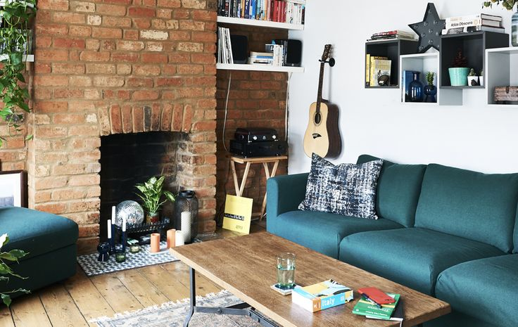 A living room with green sofa and exposed brick wall.
