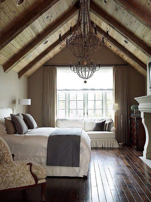 Rustic bedroom. White and grey bedding. Cream and white chair. White couch. White fireplace. Wrought iron chandelier. Exposed beams. Vaulted ceilings. Grey cream curtains. Big window. Dark hardwood floors