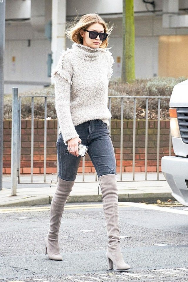 Gigi Hadid wears a turtleneck seater, gray jeans, thigh-high suede boots, and rectangular sunglasses