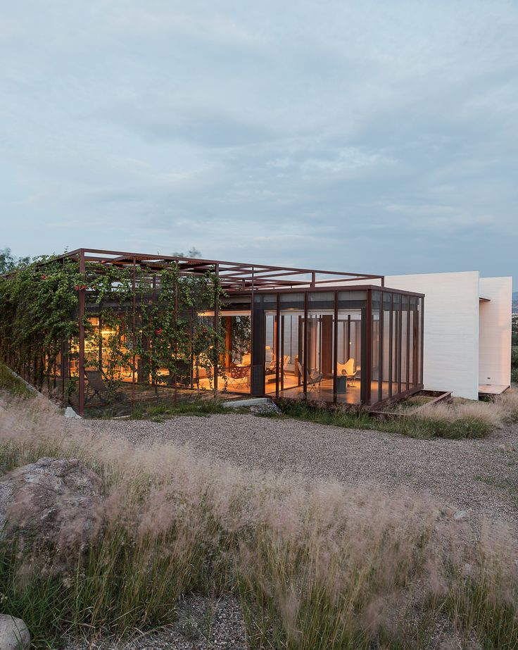 Two art studios adjoin a central volume at this work/live residence built from terracreto (sustainable concrete), glass, and painted steel just outside of San Miguel de Allende, Mexico. Residents Austin and Lida Lowrey, retired design and museum professionals, collaborated with their two daughters—Sheridan, an artist, and Elizabeth, an architect—to design the structure as a place for creative contemplation.
