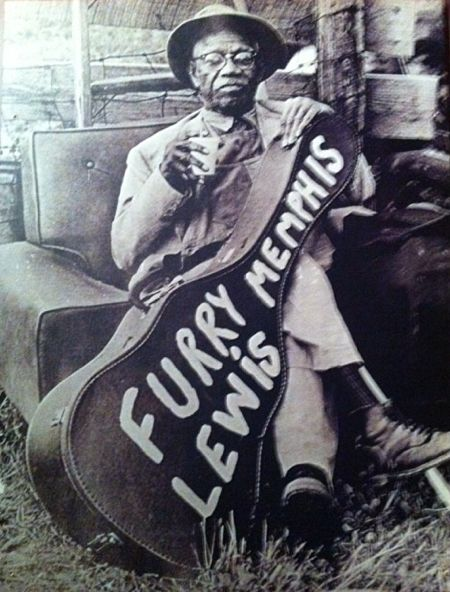Mr. Furry Lewis enjoys a cool drink while pondering his guitar case....