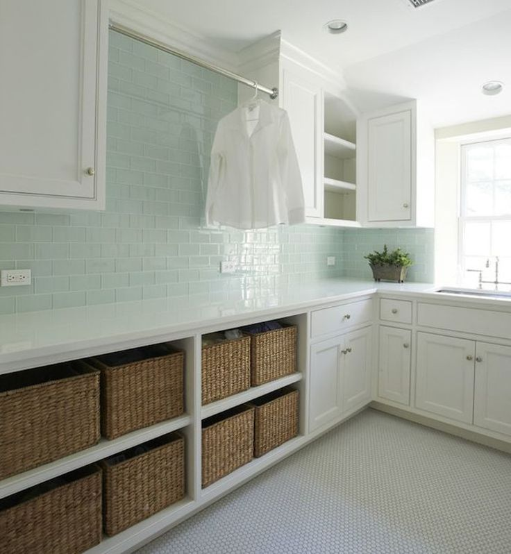 laundry room baskets - elegant white laundry room with pale green glass wubway tile and open base cabinet storage for 8 laundry baskets - Kelly Deck Design via Atticmag