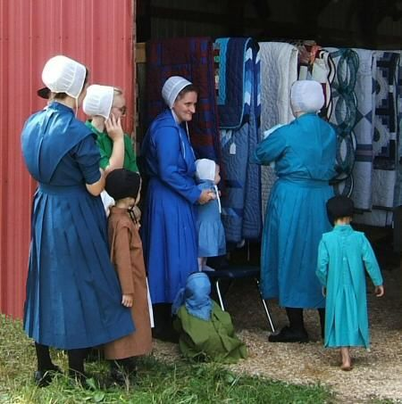 Some of the Amish women take turns working in the barn, displaying ...