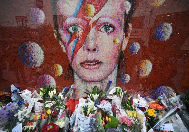 yahoonewsphotos:  Photos of the day - January 10 2017 Flowers and tributes are placed by an art work of David Bowie on his first death anniversary in Brixton London; a model poses by the 2018 Audi S5 Cabriolet during the North American International Auto Show in Detroit Michigan; and laundry of Syrian refugees is covered with snow while hung on a fence at the refugee camp of Ritsona about 53 miles north of Athens; a woman with two dogs walks past the Umbrellas the sculpture by Giorgos…