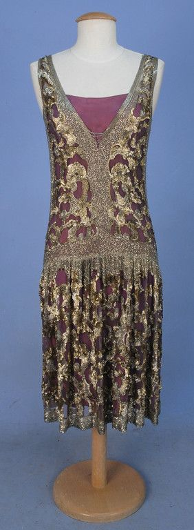 ADAIR PARIS BEADED TULLE OVERDRESS, 1920s. Sleeveless purple tulle with deep V-neck and back decorated with crystal bugle beads at neck, sides, waist and hem and allover abstract pattern of shaped metallic sequins and beads, dropped waist, skirt gathered in front, side slits.