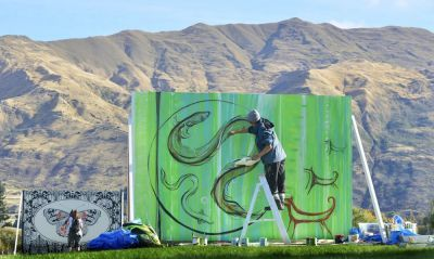 Priscilla Cowie, Ngāi Tahu, Ngāpuhi, Ngāti Kahu, painting a billboard during the 2013 Festival of Colour on the Wanaka waterfront, Photo by Peter McIntosh. More tuna arriving in 2015 Festival of Colour - Wānaka.