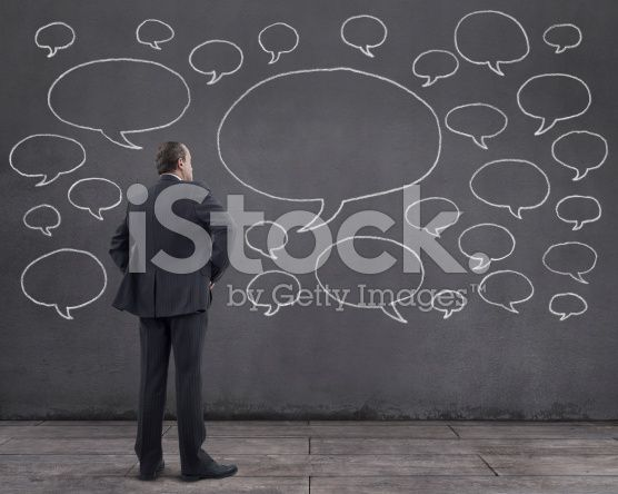 Businessman with Speech Bubbles Sketched on the Wall (royalty-free stock photo) © mgkaya