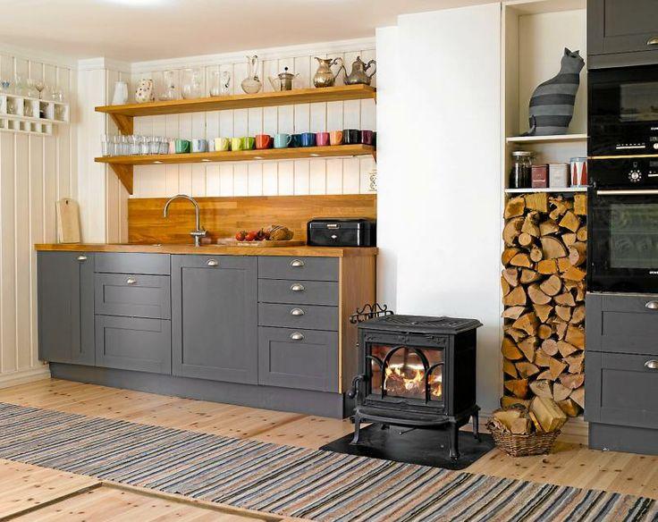 KOSELIG KJØKKEN: Det romslige kjøkkenet er fra Norema.Peisen gir en lun atmosfære og de fargerike koppene frisker opp rommet.