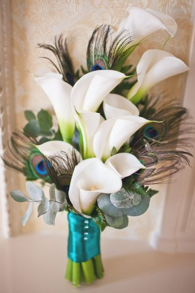 White calla lilies and peacock feather bridal bouquet.