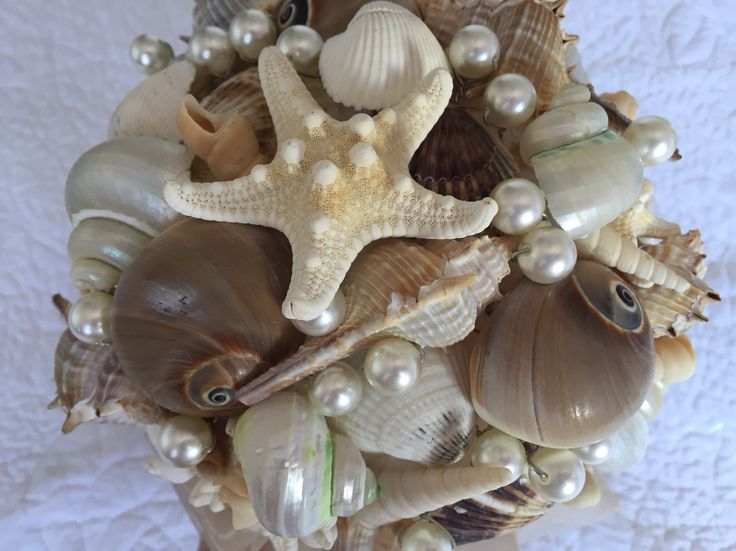 A stunning bouquet of natural seashells and shiny pearls makes this the perfect bouquet for any beach wedding. The pearl handle and organza skirt compliment it's natural beauty.    All bouquets can be reproduced in the size and colour of your choice. Feel free to mix and match ideas to make your bouquet more individual. Corsage, MOB and Lapel pins are also available to match your colours. Contact leeann@bejewelledbridal.com.au for more information.