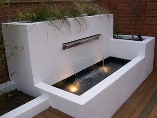 Modern water feature which adds height and structure to garden.