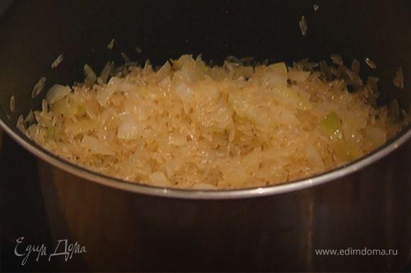 Всыпать рис и, помешивая, прогревать его пару минут, чтобы он пропитался маслом.