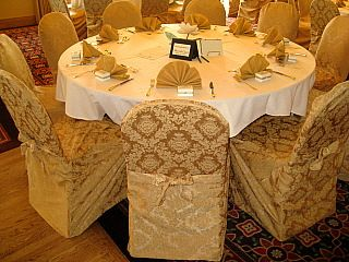 Can't go wrong with gold!  Gold damask chair covers featuring a built in sash.