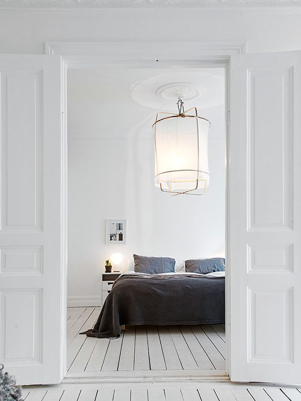 A beautiful and simple designed bedroom with classic white walls and floors. Love how they have use a dark navy to add colour to the room and that large light shade is just amazing feature to the room. Beautifully done!