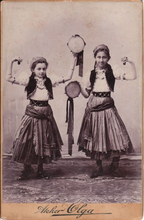 This Cabinet Card features two sweet girls dancing and playing tambourines. They appear to be gypsies and are wearing traditional ethnic clothing. The photographer is Olga and the studio is located in Oravicza, Romania. From Cabinetcardgallary