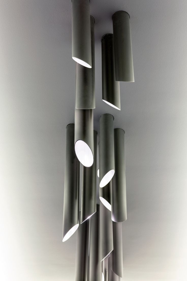 Tubes of matt black brass - light fixture for a boardroom of technical appearance.