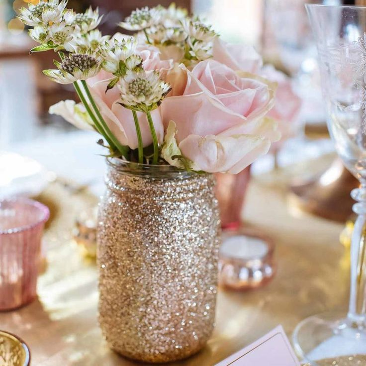 Looking to add some gold sparkle to home?We LOVE these gold glitter mason jars which can make brilliant vases, us them at home, for dinner parties or on wedding tables. The jars come with a gold lid. Use at weddings: The vases can be used in a grouping in the centre of your wedding tables, we think 3 grouped together looks best, or mix them in with our other vases and gold tea light holders for additional wow factor.The jars could also be used as containers at your wedding, use them as a pen…