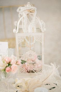 pink flowers in white vintage birdcage with pearls wedding centerpiece