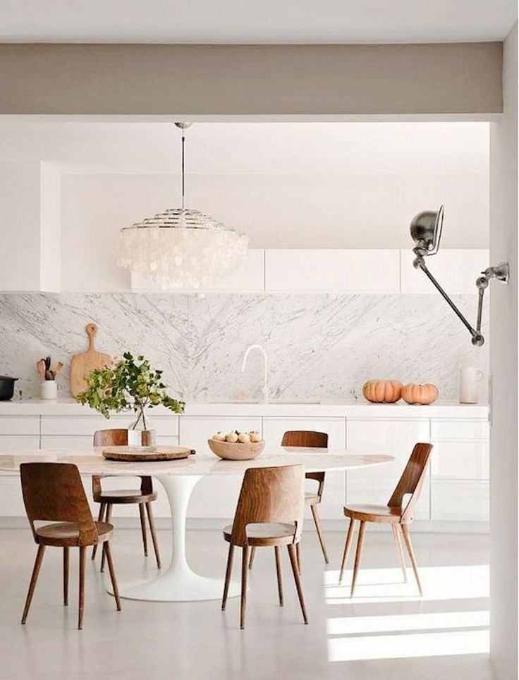 Bright, white kitchen with rustic dining space. Oval Tulip dining table – Marble Eero Saarinen. 15 Astounding Oval Dining Table for Your Modern Dining Room ♥ Discover the season's newest designs and inspirations. Visit us at  www.moderndiningtables.net #diningtables #homedecorideas #diningroomideas @ModDiningTables
