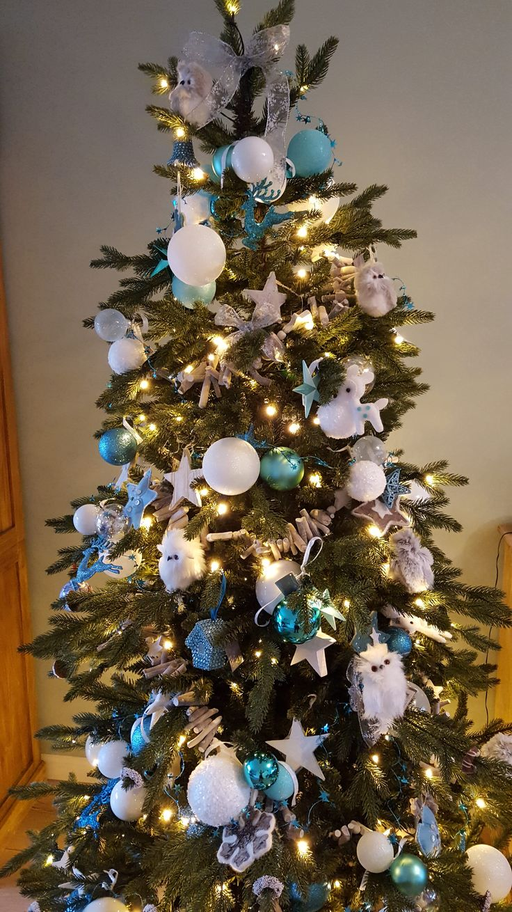 Frozen theme Christmas Tree inspiration with white, teal and light blue Christmas decorations.