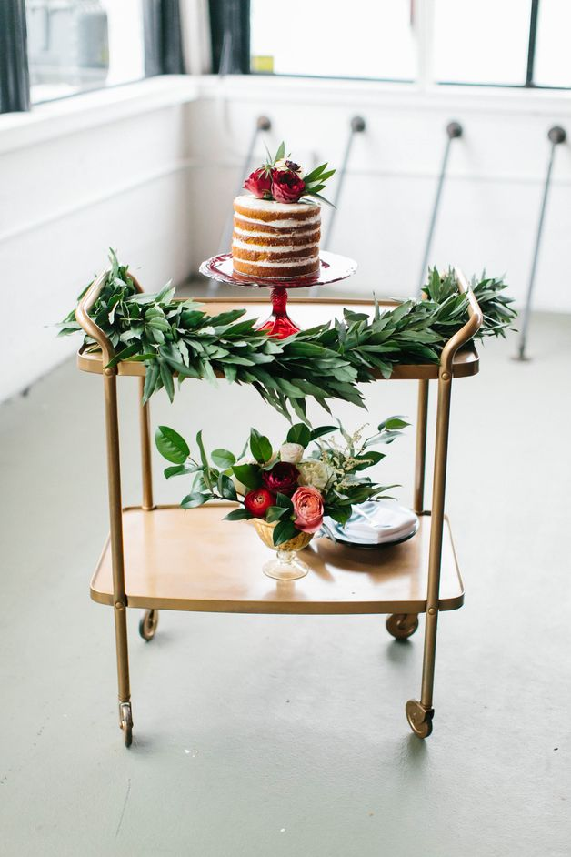 A Gold Cake Table Adorned With Foliage And Topped With A Naked Cake