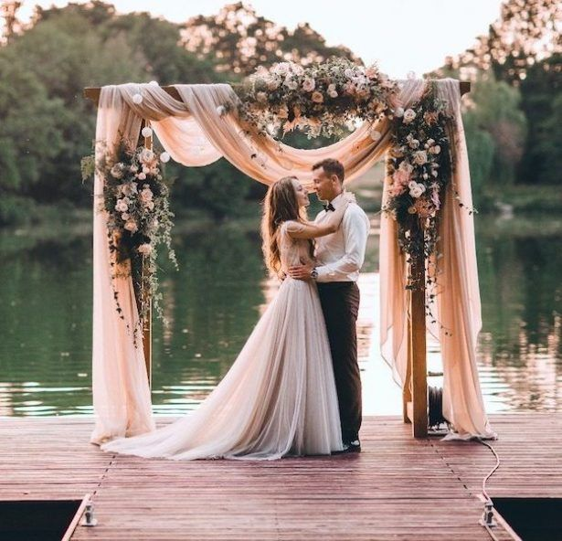 Elegant lakeside wedding ceremony with romantic florals