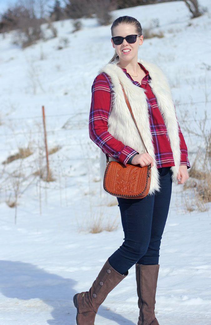 White Fur Vest: red plaid shirt, white fur vest, dark wash jeans, brown boots.