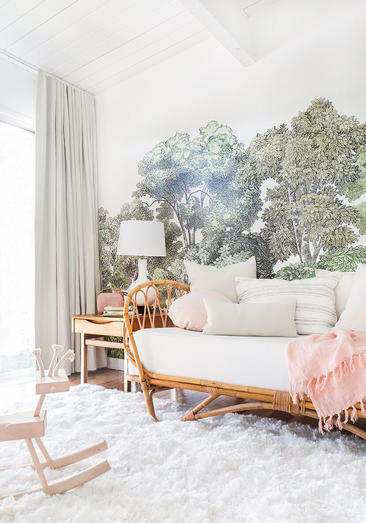 Emily Henderson's blush and green midcentury modern nursery is perfection. She used Loom Decor's Ripplefold Drapery in Dew Linen, with a blackout liner, to block out light, and tied it into the room with a show-stopping tree wallpaper.   Photographer: Tessa Neustadt