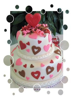 Romantic Tiered Valentine's Cake: Two tiered Valentine's Party Cake.  12 x 8 double round stacked cakes covered in fondant and decorated with fondant cut outs and curly Q's.  Lollipop chocolate
